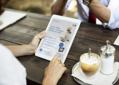 People hangout together at coffee shop looking at tablet with GE ad